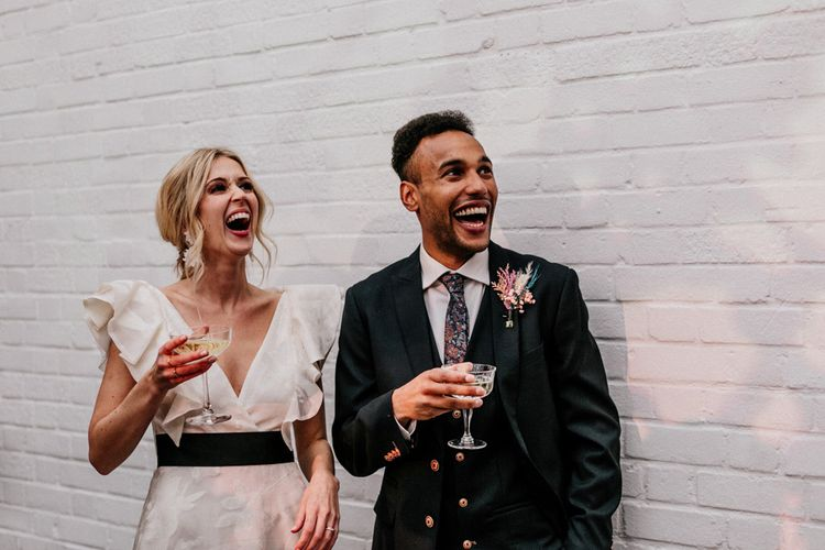 Bride in Jesus Peiro Wedding Dress with Ruffle Sleeves and Groom Laughing During Speeches