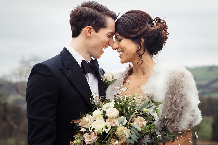 Bride in Lace Pronivias Dralia Wedding Dress and Fur Stole with Groom in Black Tuxedo and Bow Tie