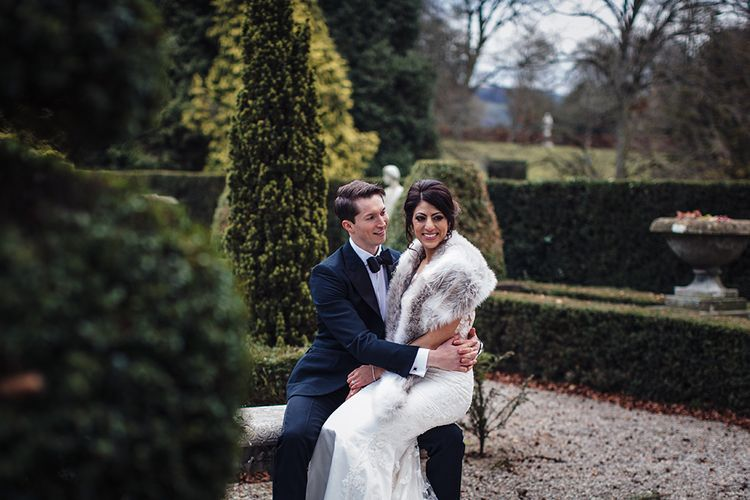 Bride in Lace Pronivias Dralia Wedding Dress and Fur Stole sitting on her Grooms Knee