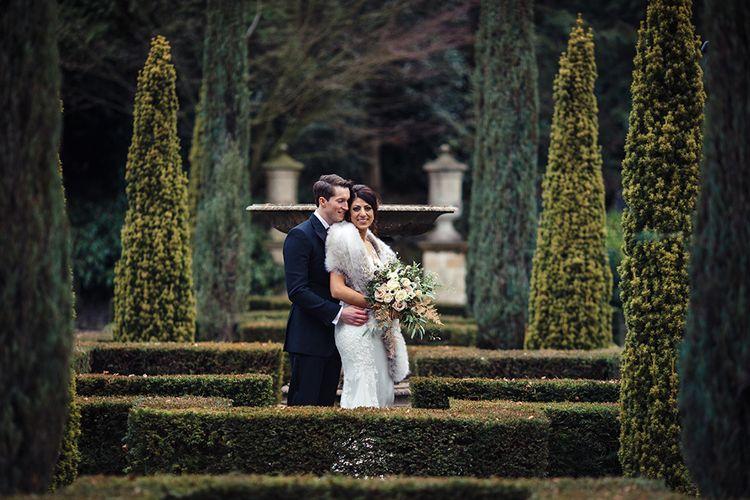 Bride in Lace Pronivias Dralia Wedding Dress and Groom in Black Tie Suit  Embracing