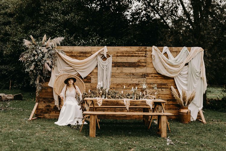 Boho Bride in Lace Wedding Dress | Wooden Backdrop with Drapes, Dried Flowers & Macrame Decor | Wooden Table with Candle Sticks & Greenery Garland | Nude Bohemian Wedding Inspiration by Wonderland Invites & Rock The Day Styling | Kelsie Low Photography