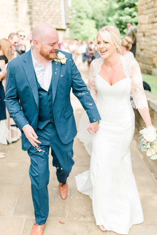 Stylish Bride in Suzanne Neville Wedding Dress and Lace Bolero and Groom in Navy Hugo Boss Suit Showered in Confetti
