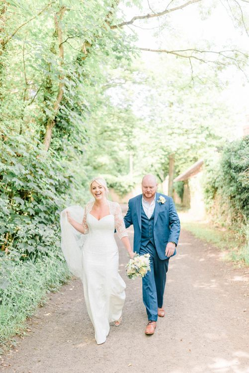 Bride in Suzanne Neville Wedding Dress and Lace Bolero and Groom in Navy Hugo Boss Suit  Walking Down a Country Lane