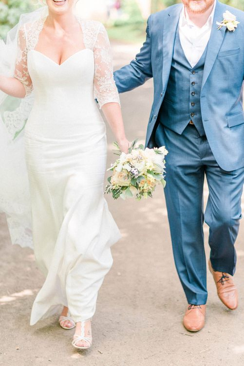 Stylish Bride in Suzanne Neville Wedding Dress and Lace Bolero and Groom in Navy Hugo Boss Suit  Walking Down a Country Lane
