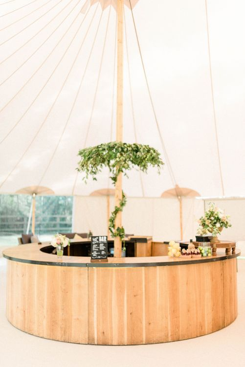 Wooden Bar with Foliage Chandelier in a Sperry Tent Reception