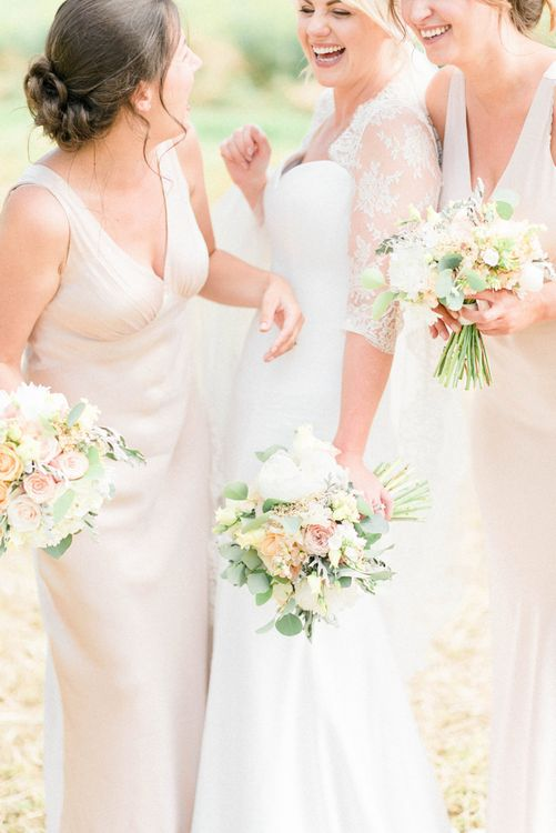Bridesmaids in Oyster Ghost Dresses and Bride in Suzanne neville Wedding Dress and Lace Bolero Holding Pastel Peach Bouquets