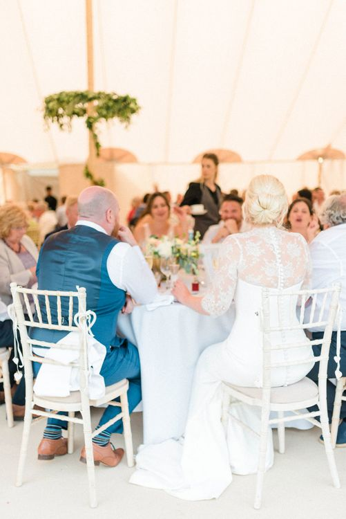 Bride and Groom Sitting at a Sweetheart Table During the Wedding Breakfast Reception