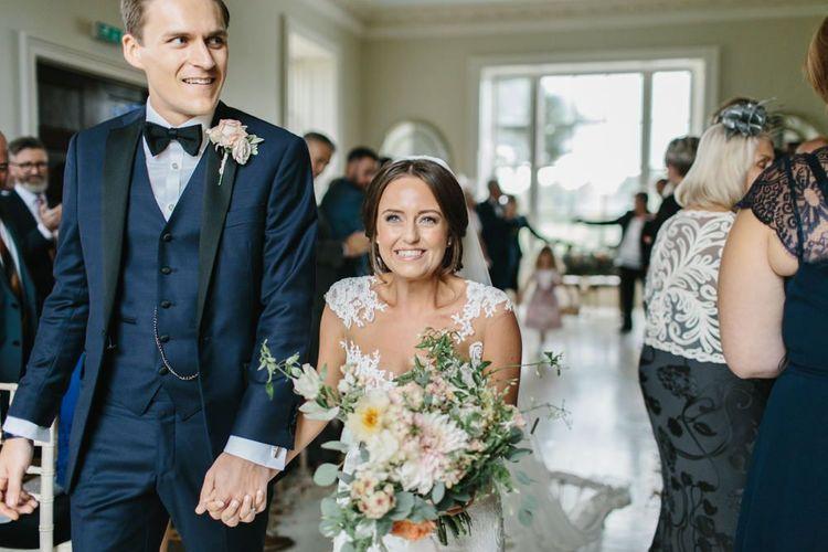 Bride in Pronovias Wedding Dress and Groom in Navy Tuxedo Just Married