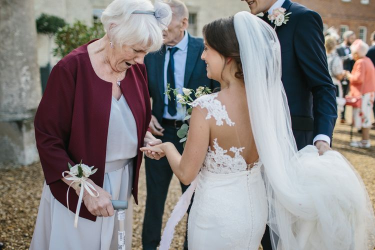 Bride in Pronovias Wedding Dress Showing Her Ring to Her Wedding Guests