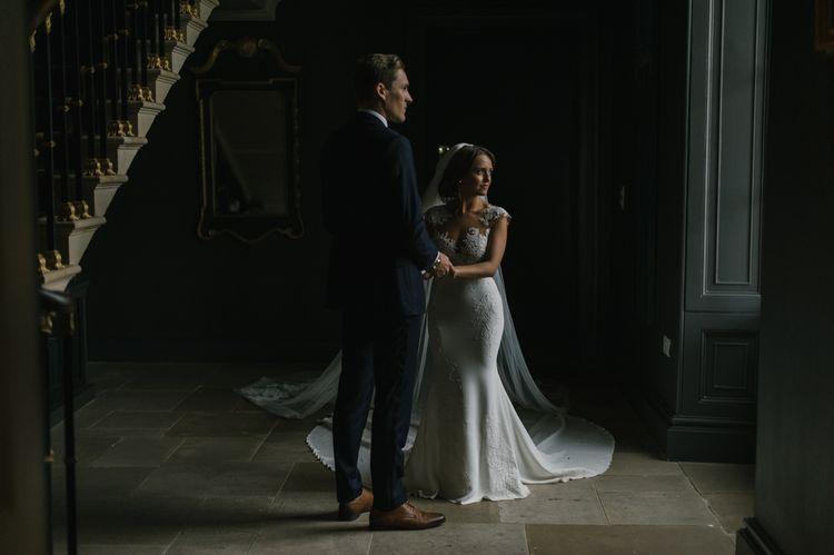 Bride in Pronovias Wedding Dress and Groom in Navy Suit Holding Hands