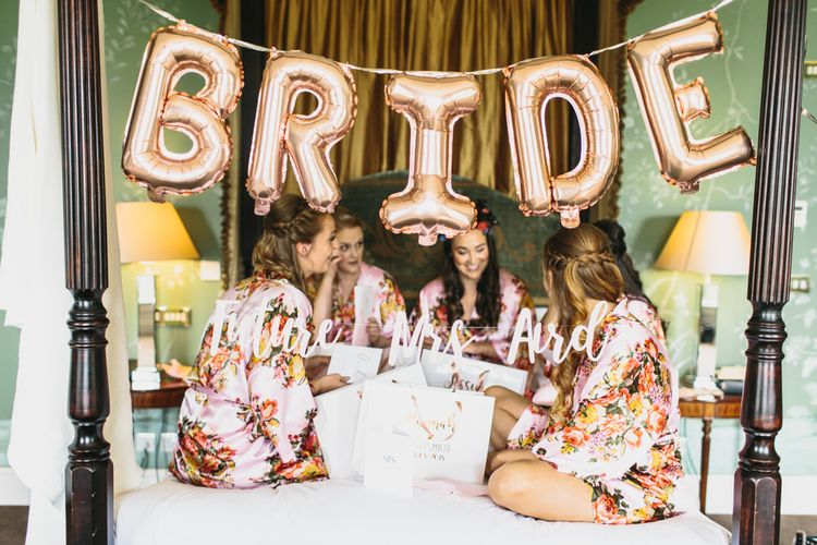 Gold Foil Bride Balloons and Bridal Party Sitting on a Bed