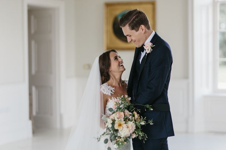 Bride in Lace Wedding Dress and Groom in Navy Tuxedo