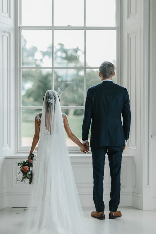 Bride and Groom Holding Hands Looking Out the Window
