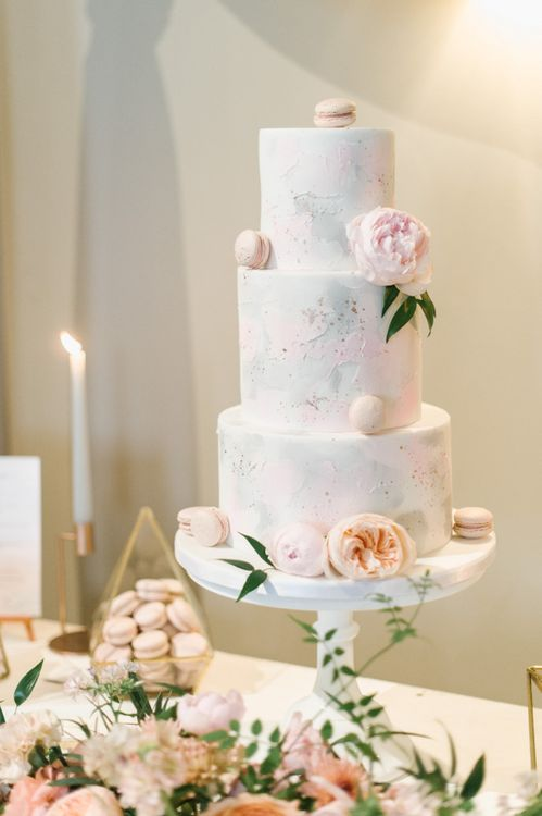 Elegant Three-Tier Wedding Cake Decorated with Peach Macaroons and Flowers