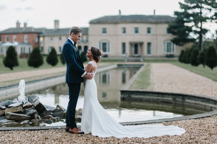Bride in Pronovias Wedding Dress with Long Train and Groom in Navy Blue Suit