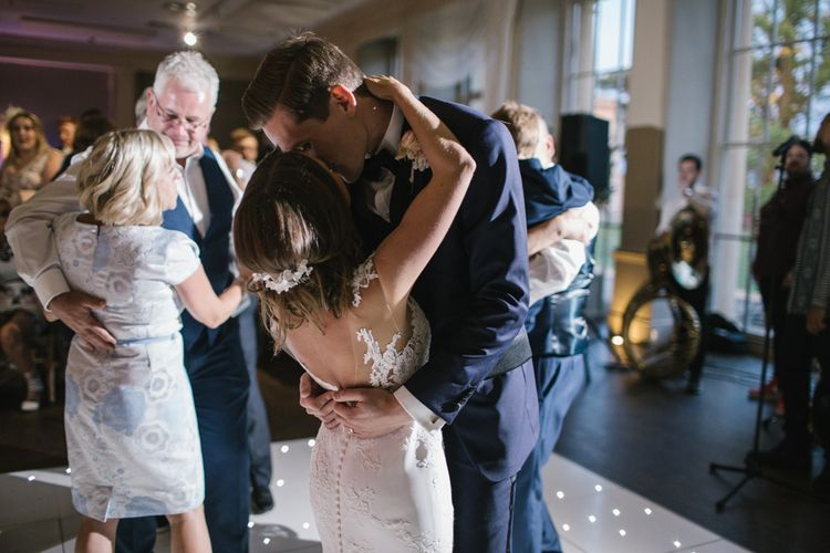 Bride in Lace Pronovias Wedding Dress and Groom on Navy Suit Embracing on the Dance Floor