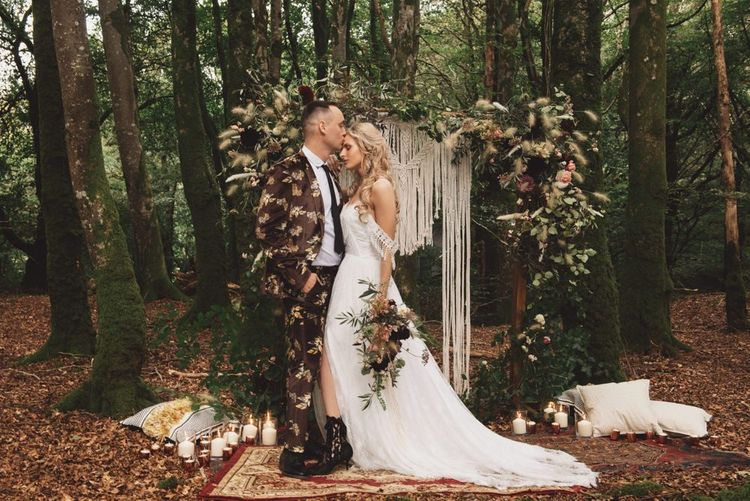 Groom in Brown Patterned Suit and Bride  Cold Shoulder Wedding Dress with Fringe Detail