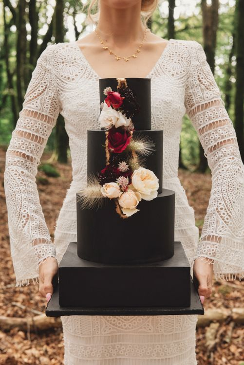 Bride in Lace Wedding Dress Holding a Black Wedding Cake