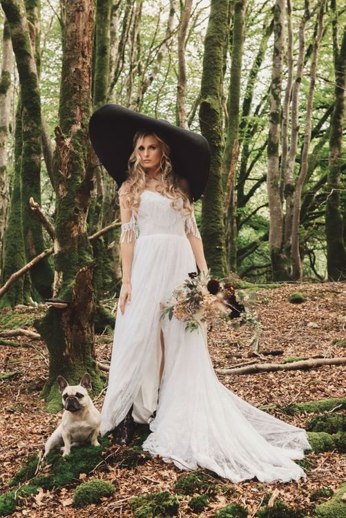Boho Bride in Cold Shoulder Wedding Dress with Tassels and Giant Black Hat