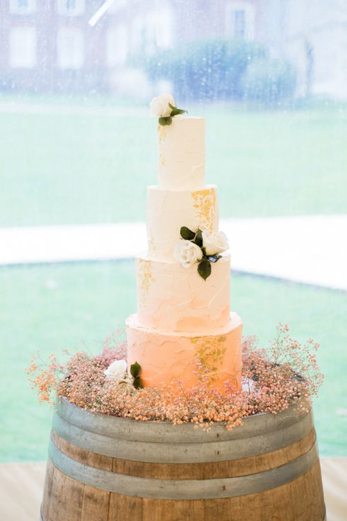 Four Tier Buttercream Wedding Cake Surrounded by Wild Flowers Restin on a Wooden Barrel