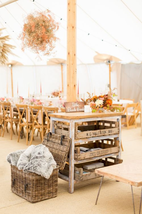 Wicker Basket Filled with Blankets and Wooden Butchers Block Guest Book Table