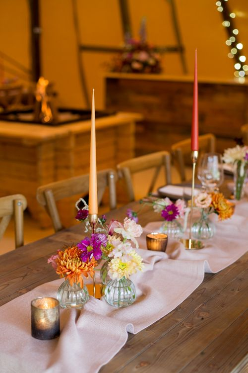 Colourful Flower Stems in Vases and Taper Candles in Gold Candlesticks