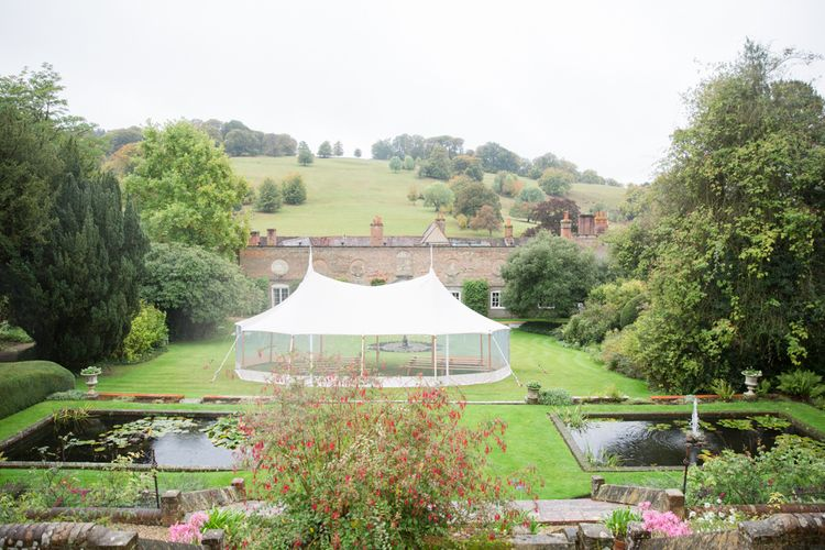 Clear Sided Wedding Ceremony Sperry Tent with Wooden Benches in the Beautiful Stonor Park Gardens