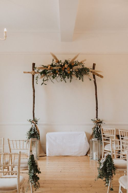 Modern boho aisle decor at Linden House with neutral flowers and candle lanterns