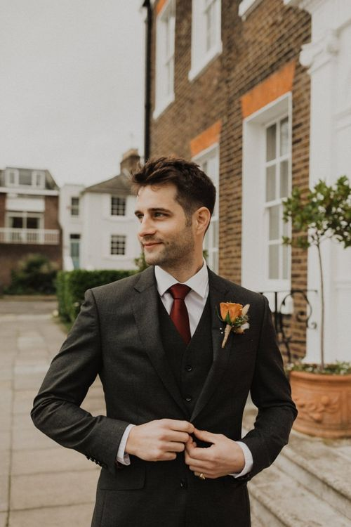 Groom wearing three piece suit and rose buttonhole at intimate wedding in London