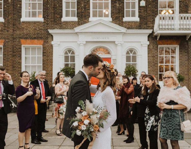 Bride and groom embrace at Linden House ceremony with closest friends and family