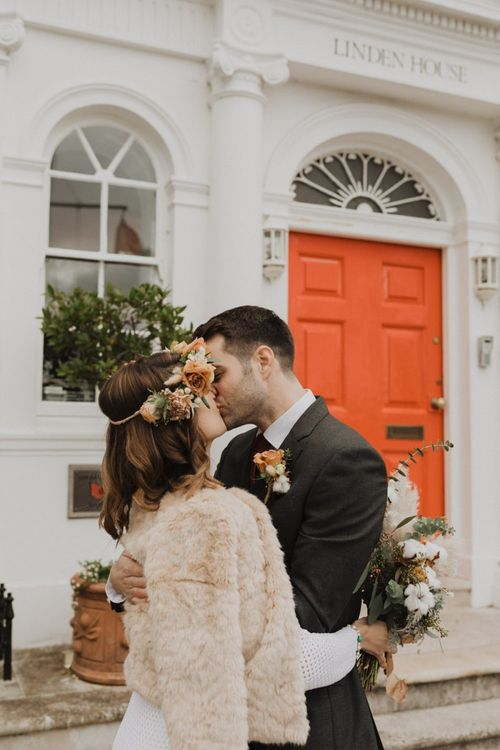 Bride wearing faux fur jacket and floral crown at Linden House wedding ceremony