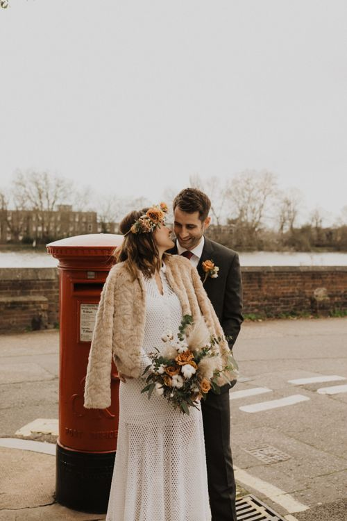 Bride and Groom steal a moment at London wedding wearing vintage dress and flower crown