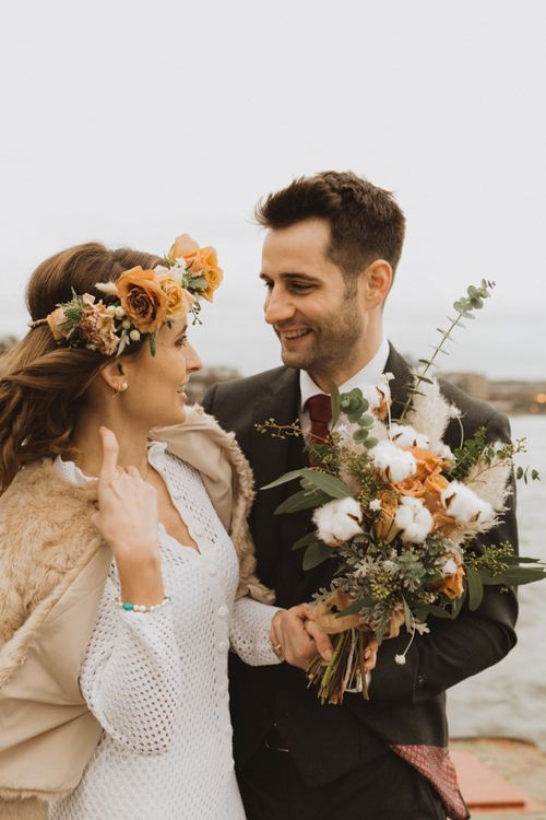 Rose and cotton flower details at London wedding with floral crown and faux fur bomber