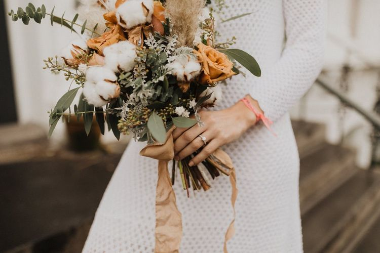 Bride wearing vintage dress and neutral bouquet with cotton flowers and foliage