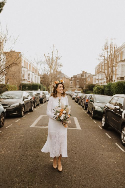 Bride wearing mid-length vintage dress with nude heels and floral crown