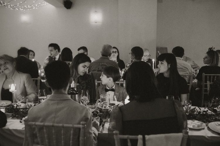 Guests enjoying intimate wedding at Linden House with festoon lighting and floral decor
