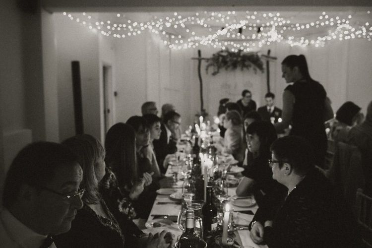 Guests celebrating at Linden House for a intimate and relaxed dinner reception with festoon lighting