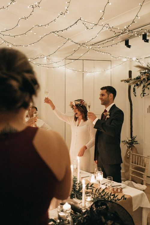 Bride and groom toast at intimate reception with boho floral decor and festoon lighting