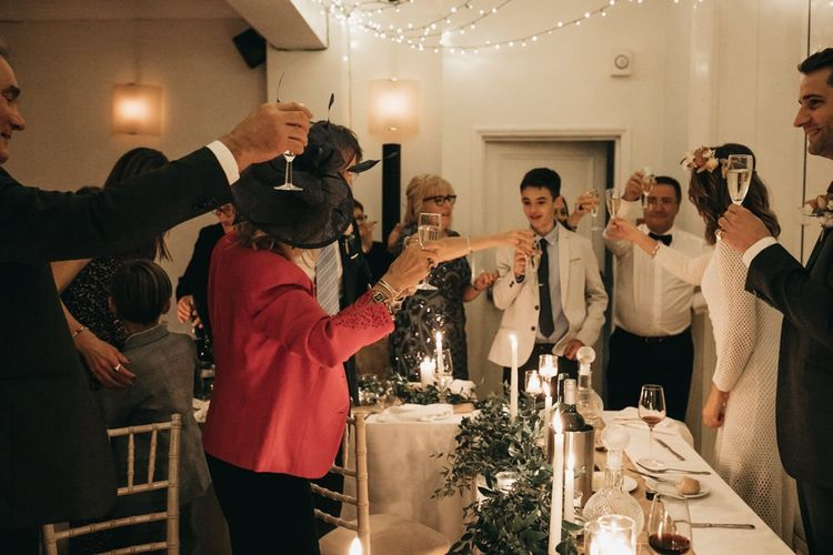 Bride and groom toast with their guests at intimate reception with foliage table decor and taper candles