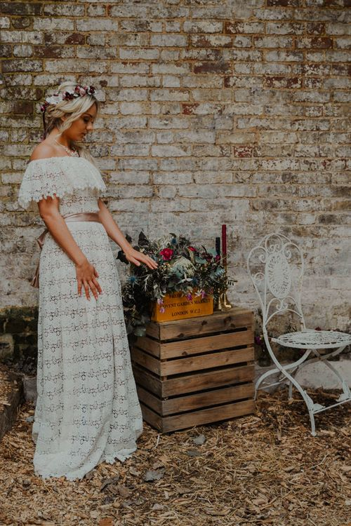Boho Bride in Lace Wedding Dress Standing Next to Crate Wedding Decor