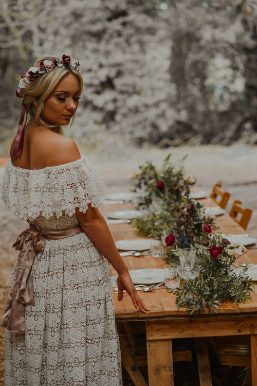 Bride in Lace Wedding Dress Standing at the Rustic Tablescape