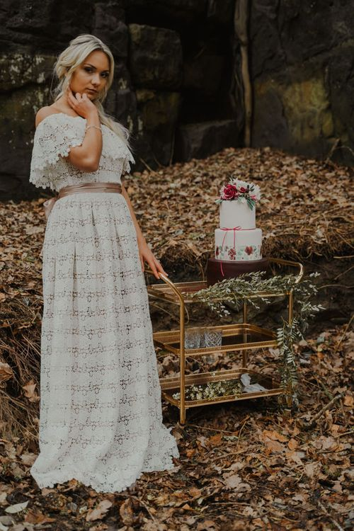 Bride Standing Next to a Gold Drinks Trolley with Three Tier Wedding Cake on Top