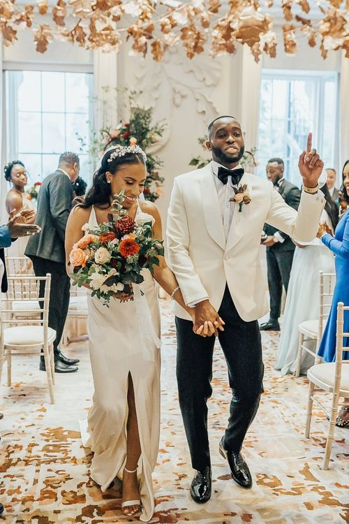 Stylish bride and groom descending up the aisle as husband and wife