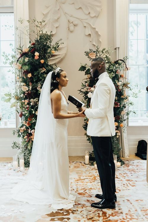 Groom in white tuxedo jacket reading his vows