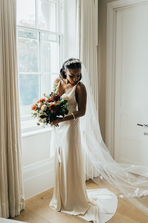 Beautiful bride in slip wedding dress holding her bouquet on the wedding morning