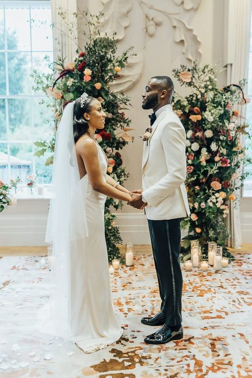 Bride and groom exchanging vows at intimate Coworth Park wedding ceremony