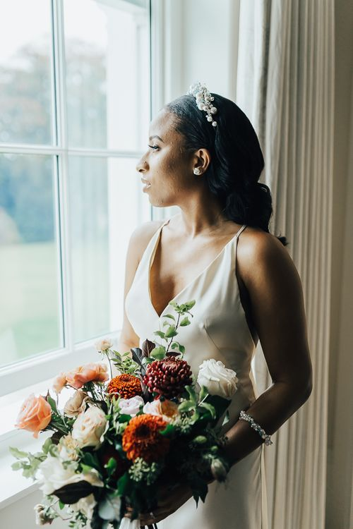 Beautiful bride in strappy wedding dress and pearl headdress