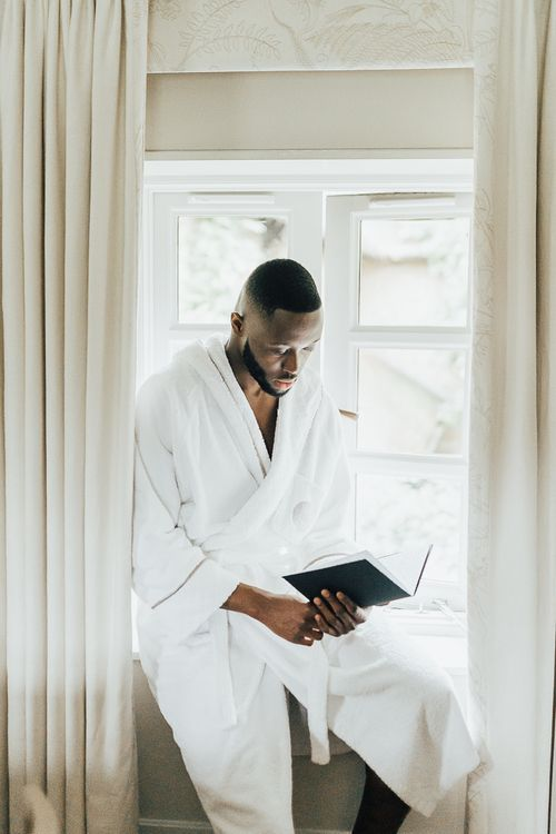 Groom in white robe on wedding morning writing his vows