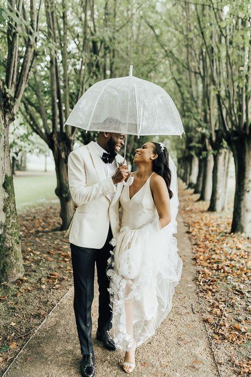 Bride and groom portrait under an umbrella at Coworth Park