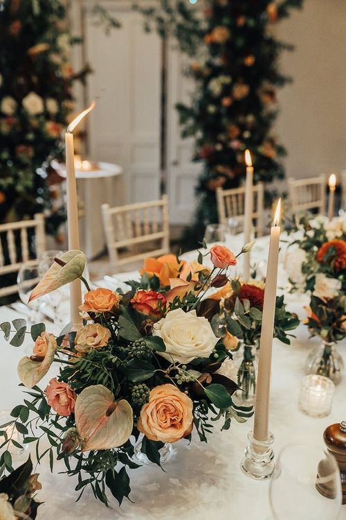 Orange wedding flowers and taper candles table decor